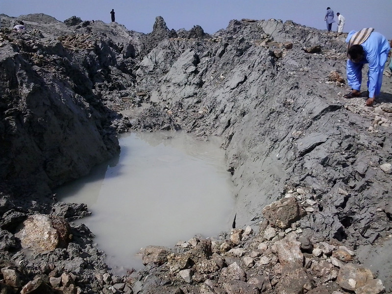 a small island of mud, stone and bubbling gas